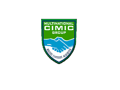 Logo of the Multinational CIMIC Gropu - a shield, top half green, bottom half white, bisected horizontally by 2 blue hands clasped.